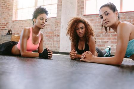 Three young women lying on gym floor