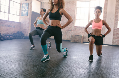Three young women exercising in gym