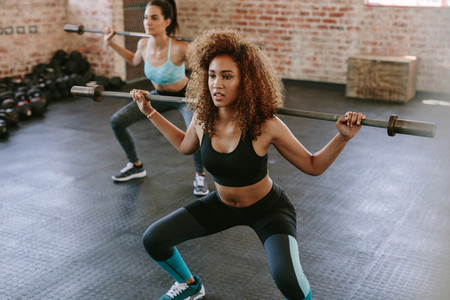 Two females workout in gym with barbell