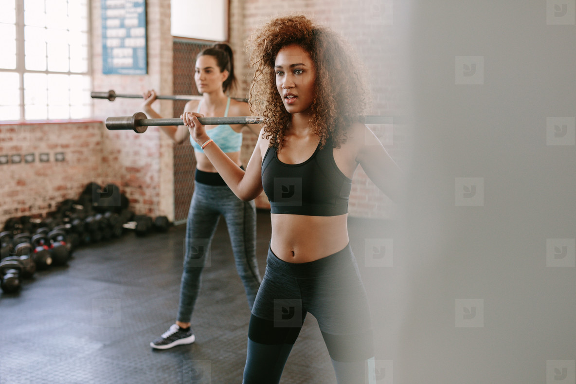 Females workout in gym with barbell