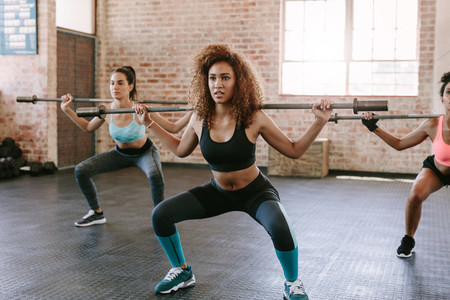 Group of women with barbells in gym