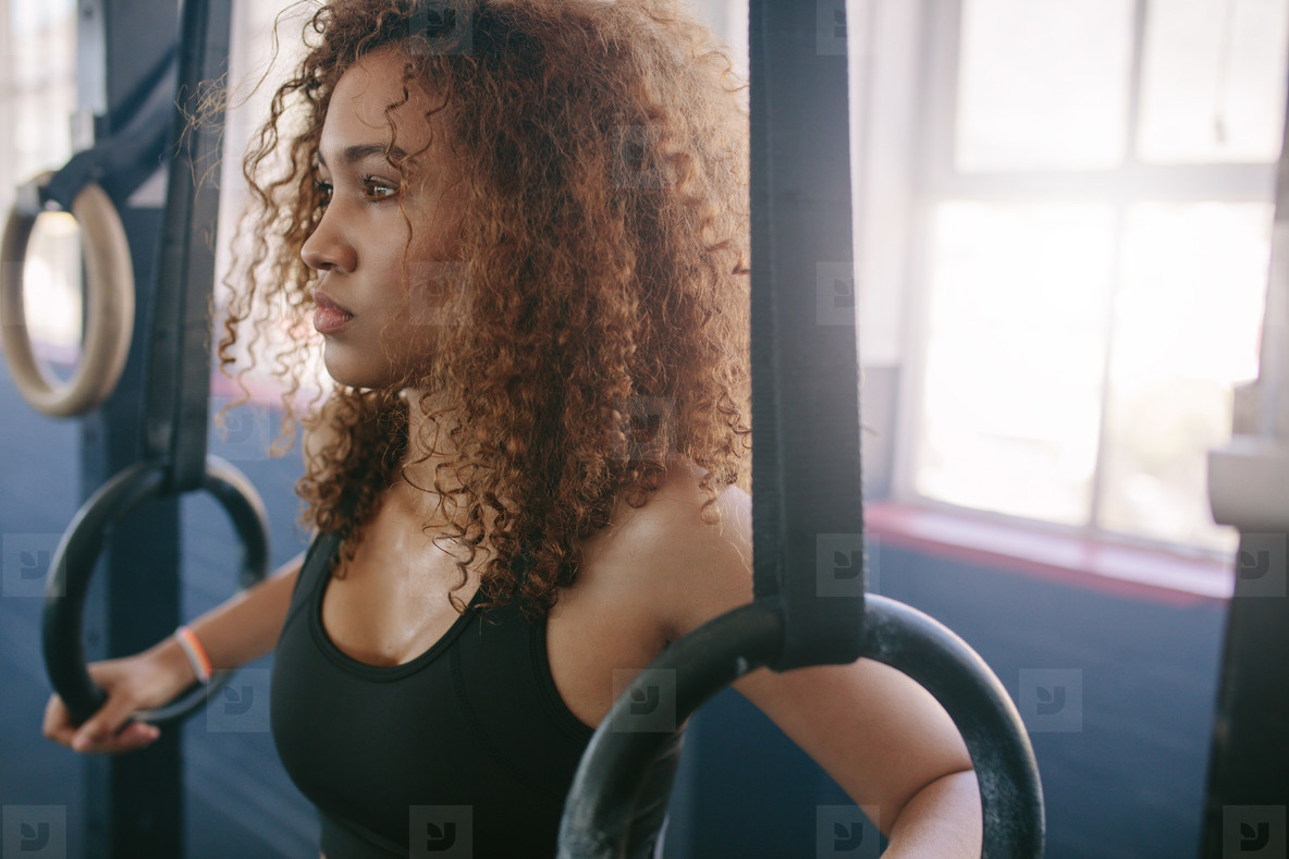 African female exercising with rings at gym