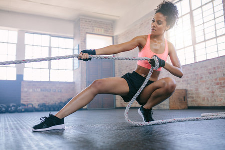 Woman doing exercises with rope at a gym