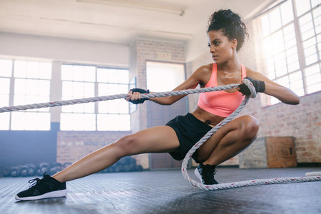 Young woman pulling rope at gym