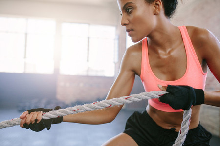 Fit young woman exercising with rope at a gym
