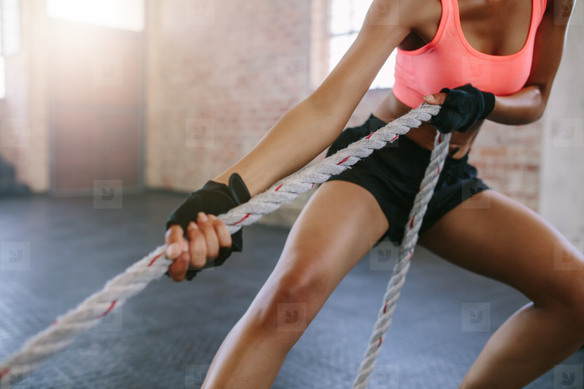 Strong young woman pulling rope at a gym