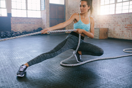 Fitness woman pulling rope at gym