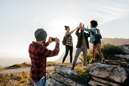Young man taking pictures of his friends hiking