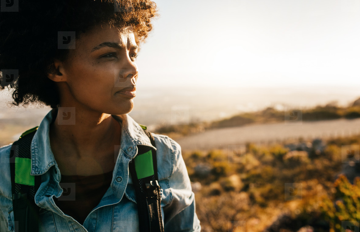 Young african female hiker standing in nature