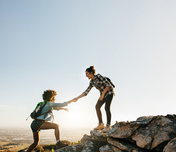 Female friends hiking help each other in mountains