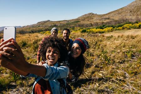 Group of friends on walk taking selfie in countryside