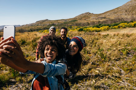 Group of friends on walk taking selfie in countryside