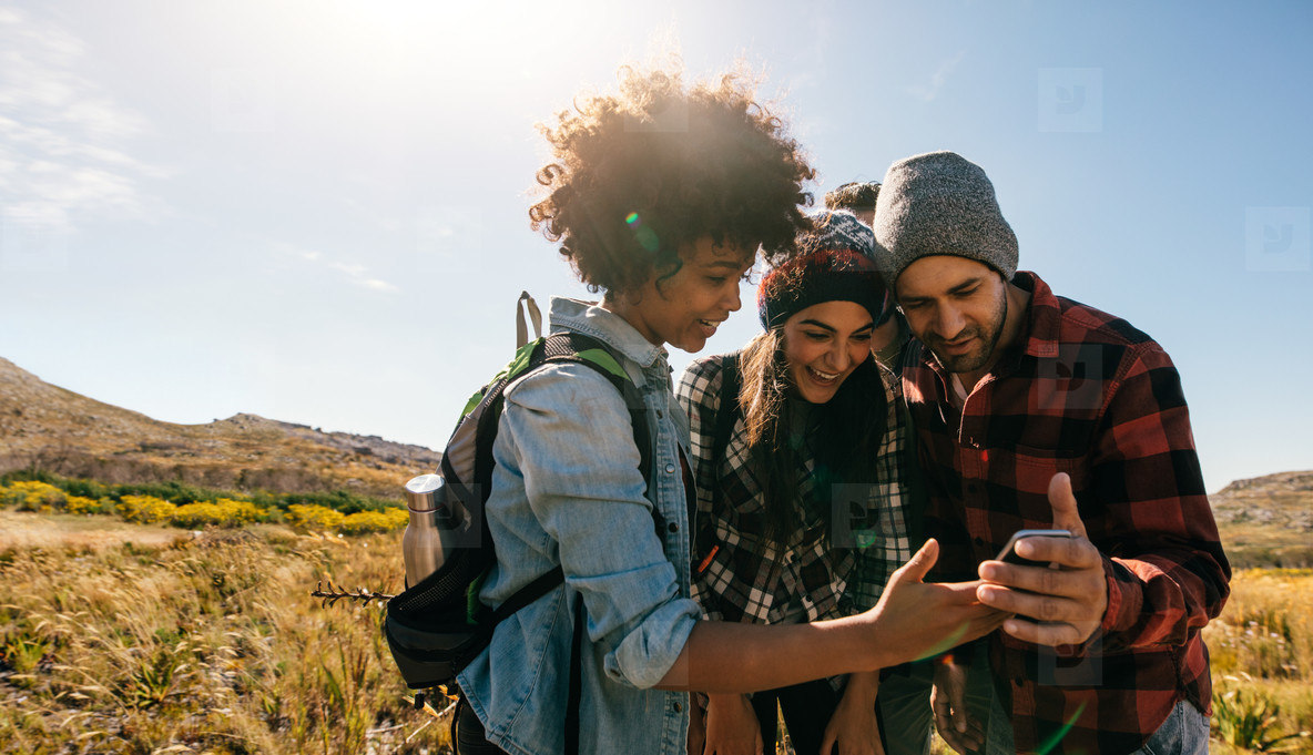 Young hikers looking at pictures on mobile phone