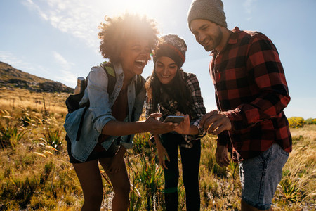 Group of hikers looking at pictures on phone and laughing