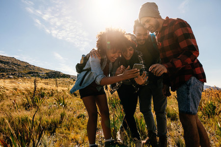 Young people hiking in countryside using mobile phone