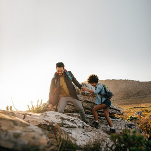 Young couple hiking help each other in mountains