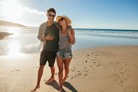 Romantic young couple walking on beach