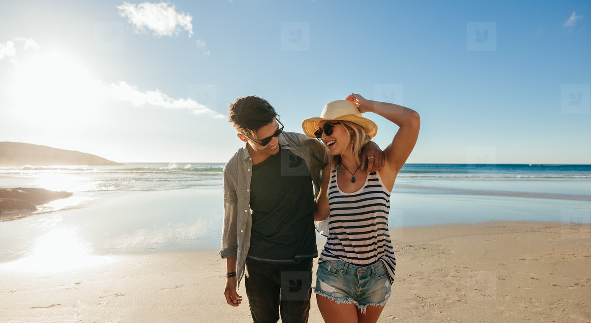 Couple walking on seashore and laughing