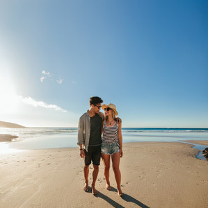 Romantic young couple walking on sea shore