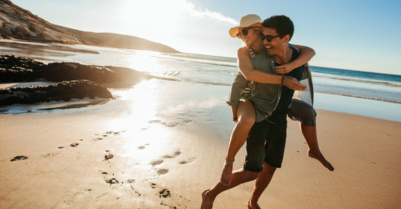 Man giving piggyback ride to girlfriend on beach