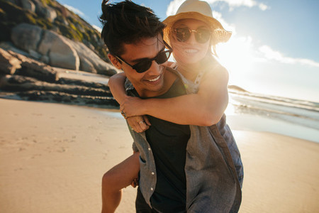 Boyfriend giving piggyback ride to girlfriend at beach