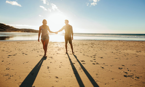 Couple walking on the beach together at sunset