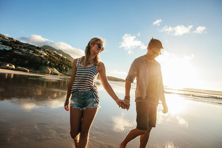 Loving couple walking on sea shore holding hands