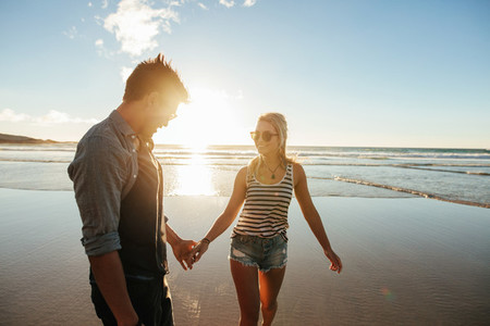 Romantic couple holding hands and walking on beach