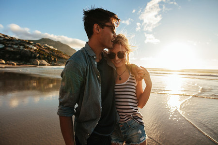 Romantic young couple standing together on beach