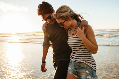 Young couple walking on the seashore