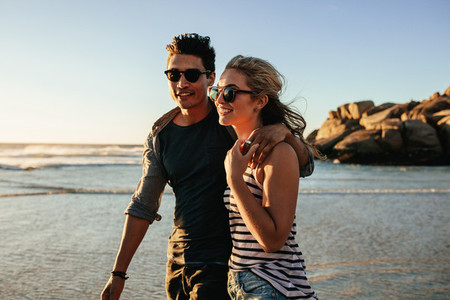 Young happy couple walking on seashore and smiling