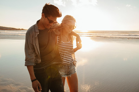Romantic young couple on beach during sunset