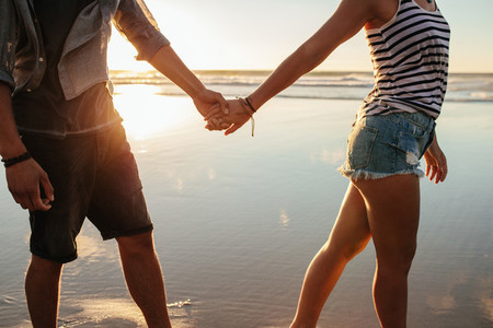 Couple holding hands and walking on the shore