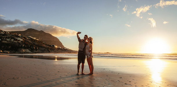 Loving young couple taking selfie at the beach