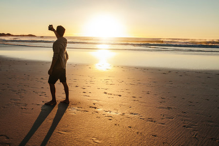 Young man taking selfie at sunset on beach