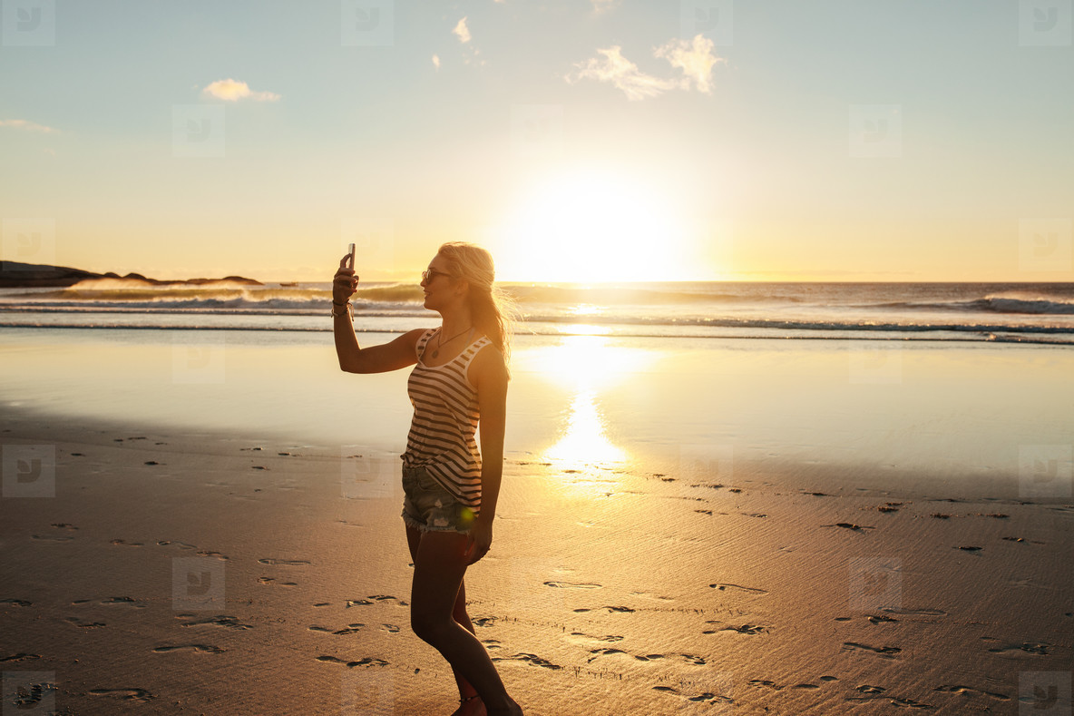 Beautiful woman taking selfie at beach