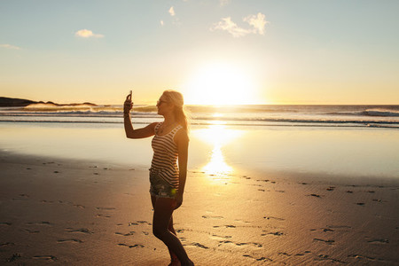 Beautiful woman taking selfie at beach