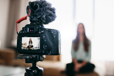 Young woman recording daily video blog on camera mounted on trip