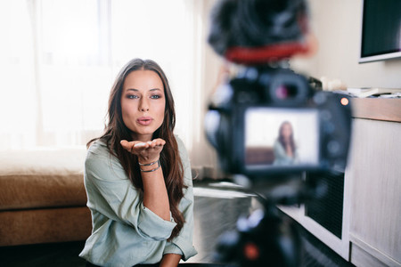 Young woman recording her video on camera mounted on tripod