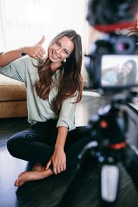 Beautiful girl recording video on tripod camera in her living ro