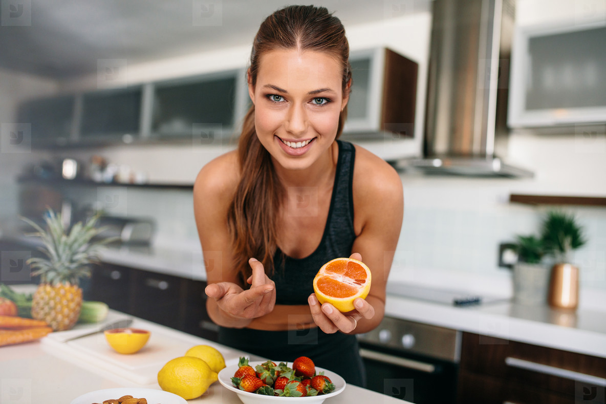 Young woman pointing towards a cut orange in kitchen