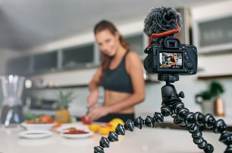 Young female blogger recording content for videoblog in Kitchen