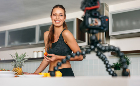 Young woman recording content for her blog in kitchen
