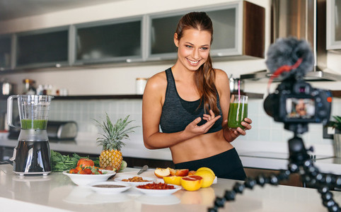 Young woman recording content for her video blog in kitchen