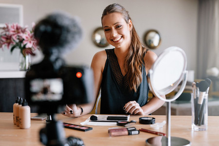 Female blogger recording video for her vlog on beauty and fashio
