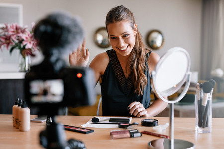 Young female recording video for her blog on the theme of beauty