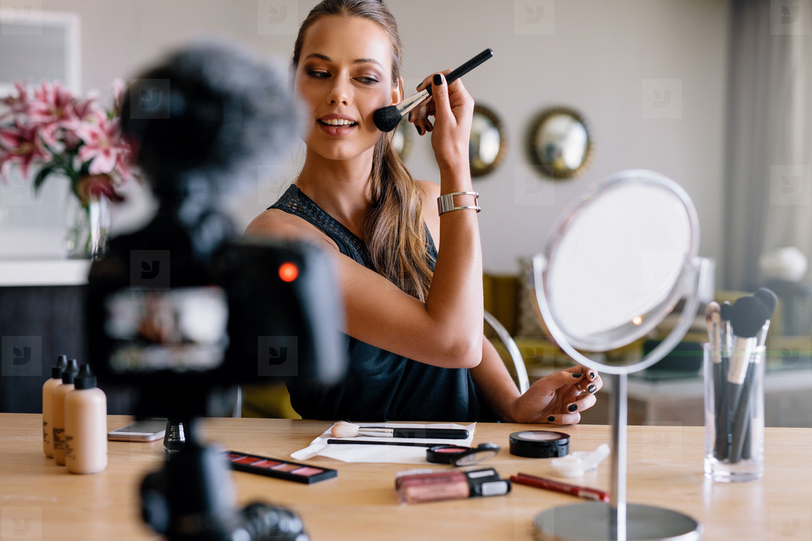 Young female vlogger recording a make up broadcast