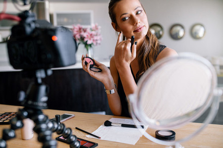 Young female vlogger recording a make up video for her vlog