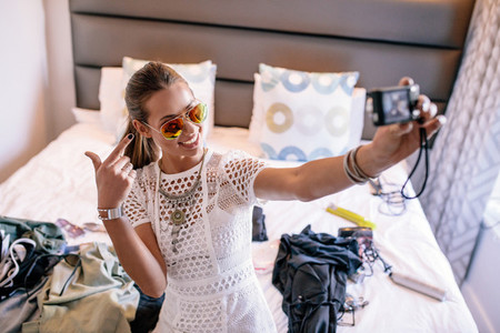 Young woman taking a selfie wearing colorful goggles