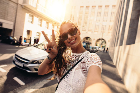 Young woman taking selfie in a street surrounded by buildings